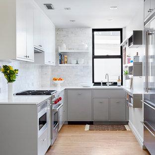 Неиссякаемый источник вдохновения для домашнего уюта: маленькая п-образная кухня-гостиная в современном стиле с врезной раковиной, плоскими фасадами, серыми фасадами, столешницей из кварцевого композита, белым фартуком, фартуком из каменной плитки, техникой из нержавеющей стали и светлым паркетным полом без острова