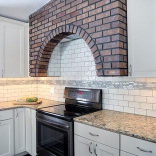 ミネアポリスの大きいカントリー風おしゃれなキッチン (シングルシンク、シェーカースタイル扉のキャビネット、白いキャビネット、人工大理石カウンター、白いキッチンパネル、セラミックタイルのキッチンパネル、黒い調理設備、クッションフロア、茶色い床、ベージュのキッチンカウンター) の写真