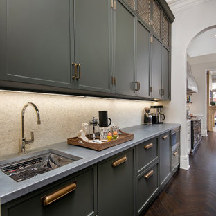 Photo of a mid-sized modern kitchen pantry in Chicago with green cabinets, zinc benchtops, metallic splashback, marble splashback, stainless steel appliances, dark hardwood floors, brown floor and grey benchtop.
