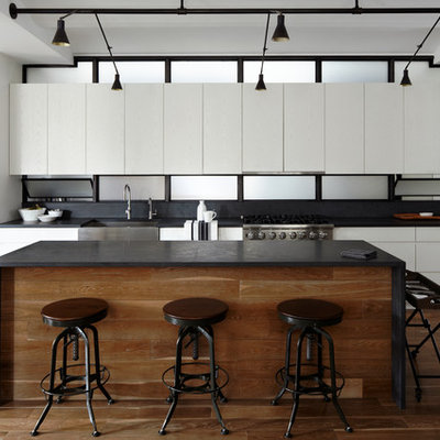 Example of a trendy single-wall open concept kitchen design in New York with a farmhouse sink, flat-panel cabinets and white cabinets