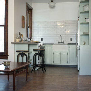 Inspiration for a large traditional u-shaped open plan kitchen in New York with a farmhouse sink, louvered cabinets, green cabinets, wood benchtops, white splashback, stone tile splashback, white appliances, dark hardwood floors and a peninsula.