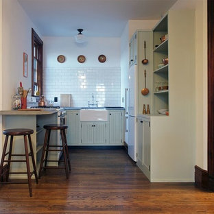 Design ideas for a large traditional u-shaped open plan kitchen in New York with a farmhouse sink, louvered cabinets, green cabinets, wood benchtops, white splashback, stone tile splashback, white appliances, dark hardwood floors and a peninsula.