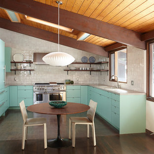 Photo of a midcentury u-shaped eat-in kitchen in New York with an undermount sink, flat-panel cabinets, green cabinets, white splashback, stainless steel appliances, dark hardwood floors, no island and brown floor.