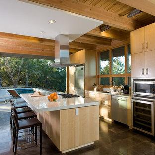 Пример оригинального дизайна: параллельная кухня среднего размера в стиле модернизм с техникой из нержавеющей стали, врезной раковиной, плоскими фасадами, светлыми деревянными фасадами, островом и полом из известняка