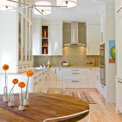 Eat-in kitchen - transitional u-shaped eat-in kitchen idea in Boston with shaker cabinets, paneled appliances, white cabinets, green backsplash and matchstick tile backsplash