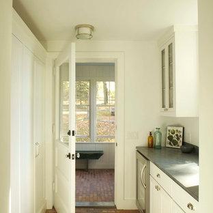 Klassische Küche mit weißen Schränken, Granit-Arbeitsplatte, Küchengeräten aus Edelstahl und Backsteinboden in New York