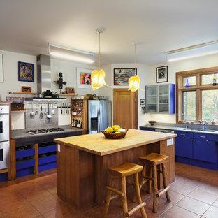 ニューヨークのエクレクティックスタイルのおしゃれなアイランドキッチン (アンダーカウンターシンク、フラットパネル扉のキャビネット、青いキャビネット、シルバーの調理設備の、テラコッタタイルの床、オレンジの床) の写真
