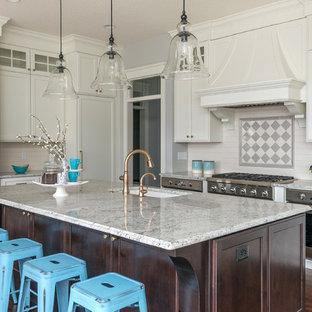 Exempel på ett klassiskt flerfärgad flerfärgat kök, med en undermonterad diskho, luckor med infälld panel, vita skåp, flerfärgad stänkskydd, rostfria vitvaror, mörkt trägolv, en köksö och brunt golv