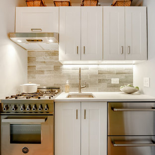 Inspiration for a small transitional single-wall kitchen in New York with an undermount sink, shaker cabinets, white cabinets, grey splashback, stainless steel appliances, multiple islands and white benchtop.