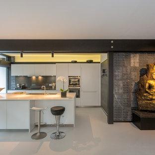 ロンドンのアジアンスタイルのおしゃれなアイランドキッチン (ダブルシンク、フラットパネル扉のキャビネット、白いキャビネット、グレーのキッチンパネル、シルバーの調理設備の、グレーの床) の写真