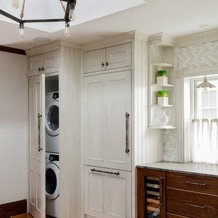 ボストンの広いビーチスタイルのおしゃれなダイニングキッチン (エプロンフロントシンク、フラットパネル扉のキャビネット、中間色木目調キャビネット、大理石カウンター、ベージュキッチンパネル、ガラスタイルのキッチンパネル、シルバーの調理設備、無垢フローリング、アイランドなし、ベージュのキッチンカウンター) の写真