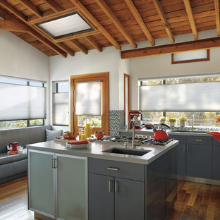 Inspiration for a mid-sized industrial l-shaped open plan kitchen in Orange County with an undermount sink, flat-panel cabinets, blue cabinets, concrete benchtops, multi-coloured splashback, mosaic tile splashback, stainless steel appliances, medium hardwood floors and with island.