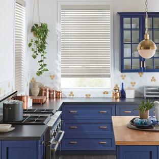 Cette photo montre une cuisine chic en L de taille moyenne et fermée avec un placard à porte shaker, des portes de placard bleues, une crédence multicolore, un électroménager en acier inoxydable, un îlot central, un sol gris, un plan de travail en quartz modifié, une crédence en carreau de porcelaine et un plan de travail noir.