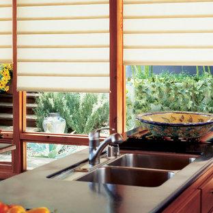 Asiatisk inredning av ett stort kök, med en undermonterad diskho, släta luckor, skåp i mellenmörkt trä, bänkskiva i koppar, rostfria vitvaror, betonggolv, en köksö och grått golv