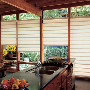ダラスの大きいアジアンスタイルのおしゃれなキッチン (アンダーカウンターシンク、フラットパネル扉のキャビネット、中間色木目調キャビネット、人工大理石カウンター、シルバーの調理設備の、コンクリートの床、グレーの床) の写真