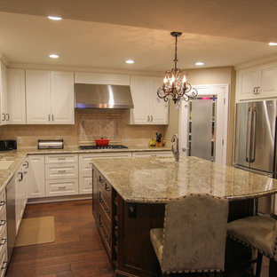 Open concept kitchen - large traditional u-shaped dark wood floor open concept kitchen idea in San Francisco with an undermount sink, raised-panel cabinets, white cabinets, granite countertops, beige backsplash, stone tile backsplash and stainless steel appliances