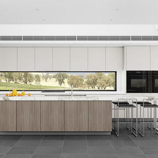 Large modern open concept kitchen remodeling - Example of a large minimalist l-shaped slate floor open concept kitchen design in Newcastle - Maitland with an undermount sink, flat-panel cabinets, medium tone wood cabinets, marble countertops, black appliances and an island