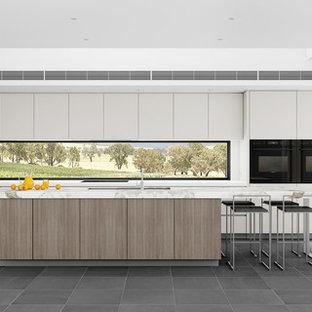 Modelo de cocina en L, minimalista, grande, abierta, con fregadero bajoencimera, armarios con paneles lisos, puertas de armario de madera oscura, encimera de mármol, electrodomésticos negros, suelo de pizarra y una isla