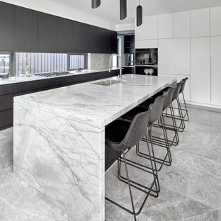 This is an example of a large contemporary galley eat-in kitchen in Sydney with marble benchtops, limestone floors, with island, grey floor, white benchtop, flat-panel cabinets, white cabinets, stainless steel appliances and timber splashback.