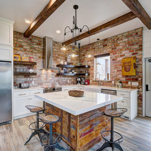 Rustic kitchen designs - Inspiration for a rustic l-shaped medium tone wood floor and brown floor kitchen remodel in Oklahoma City with a farmhouse sink, shaker cabinets, white cabinets, red backsplash, brick backsplash, stainless steel appliances, an island and white countertops
