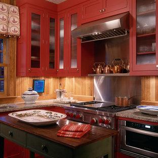 ワシントンD.C.のラスティックスタイルのおしゃれなキッチン (ガラス扉のキャビネット、シルバーの調理設備の、御影石カウンター、赤いキャビネット) の写真
