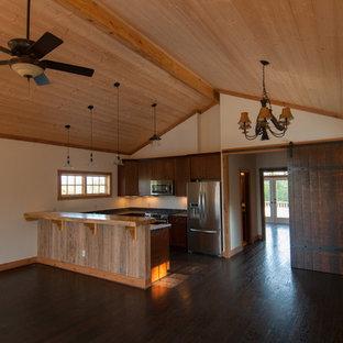 Modelo de cocina en U, campestre, abierta, con fregadero sobremueble, armarios con paneles empotrados, puertas de armario de madera en tonos medios, encimera de esteatita y electrodomésticos de acero inoxidable