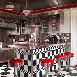 Bild på ett eklektiskt röd rött kök, med stänkskydd med metallisk yta och rostfria vitvaror