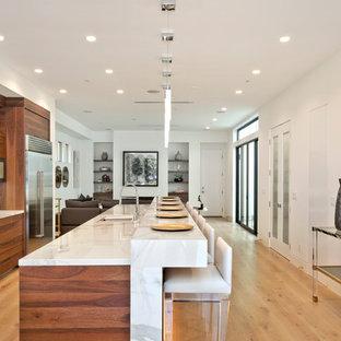 Foto di una cucina moderna di medie dimensioni con lavello sottopiano, ante lisce, ante in legno bruno, top in marmo, paraspruzzi bianco, paraspruzzi in marmo, elettrodomestici in acciaio inossidabile, parquet chiaro, isola e pavimento beige