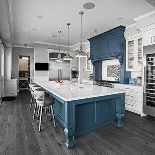 Klassisk inredning av ett stort vit vitt l-kök, med en rustik diskho, skåp i shakerstil, vita skåp, bänkskiva i kvarts, vitt stänkskydd, stänkskydd i porslinskakel, rostfria vitvaror, mellanmörkt trägolv, en köksö och grått golv