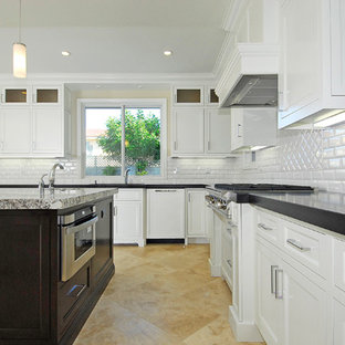 Inredning av ett klassiskt stort kök, med en undermonterad diskho, luckor med infälld panel, vita skåp, bänkskiva i koppar, vitt stänkskydd, stänkskydd i keramik, rostfria vitvaror, travertin golv, en köksö och beiget golv