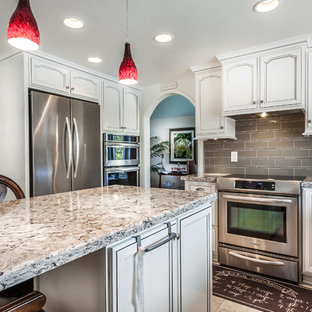 Design ideas for a mid-sized traditional u-shaped separate kitchen in Orange County with a double-bowl sink, raised-panel cabinets, white cabinets, quartz benchtops, brown splashback, glass tile splashback, stainless steel appliances, terra-cotta floors and with island.
