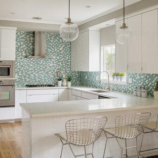 Mittelgroße Moderne Wohnküche ohne Insel in U-Form mit Einbauwaschbecken, flächenbündigen Schrankfronten, weißen Schränken, Granit-Arbeitsplatte, Küchenrückwand in Blau, Rückwand aus Mosaikfliesen, Küchengeräten aus Edelstahl und hellem Holzboden in Los Angeles