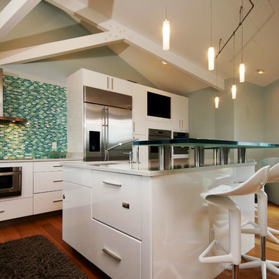 Example of a mid-sized beach style single-wall bamboo floor eat-in kitchen design in New Orleans with flat-panel cabinets, white cabinets, glass countertops, ceramic backsplash and stainless steel appliances