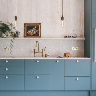 他の地域の中くらいのコンテンポラリースタイルのおしゃれなキッチン (エプロンフロントシンク、フラットパネル扉のキャビネット、緑のキャビネット、テラゾーカウンター、ベージュキッチンパネル、石スラブのキッチンパネル、パネルと同色の調理設備、コンクリートの床、アイランドなし、グレーの床、ベージュのキッチンカウンター) の写真