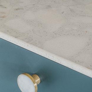 他の地域の中サイズのコンテンポラリースタイルのおしゃれなキッチン (エプロンフロントシンク、フラットパネル扉のキャビネット、緑のキャビネット、テラゾカウンター、ベージュキッチンパネル、石スラブのキッチンパネル、パネルと同色の調理設備、コンクリートの床、アイランドなし、グレーの床、ベージュのキッチンカウンター) の写真