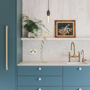 Design ideas for a medium sized contemporary single-wall open plan kitchen in Other with a belfast sink, flat-panel cabinets, green cabinets, terrazzo worktops, beige splashback, stone slab splashback, integrated appliances, concrete flooring, no island, grey floors and beige worktops.