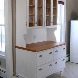 ボストンの中サイズのカントリー風おしゃれなキッチン (フラットパネル扉のキャビネット、白いキャビネット、木材カウンター、セラミックタイルの床、ベージュの床) の写真