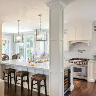 Inredning av ett klassiskt kök med öppen planlösning, med luckor med infälld panel, rostfria vitvaror, bänkskiva i kvartsit, vita skåp, vitt stänkskydd och stänkskydd i tunnelbanekakel
