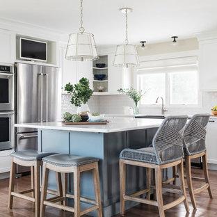 Exempel på ett stort maritimt vit vitt kök, med en rustik diskho, skåp i shakerstil, vita skåp, bänkskiva i kvarts, vitt stänkskydd, stänkskydd i glaskakel, rostfria vitvaror, en köksö, ljust trägolv och brunt golv