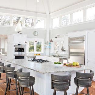 Foto de cocina en L, costera, con armarios estilo shaker, puertas de armario blancas, electrodomésticos de acero inoxidable, suelo de madera clara y una isla