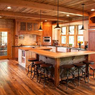 他の地域の大きいラスティックスタイルのおしゃれなキッチン (エプロンフロントシンク、シェーカースタイル扉のキャビネット、中間色木目調キャビネット、木材カウンター、シルバーの調理設備、無垢フローリング、木材のキッチンパネル) の写真