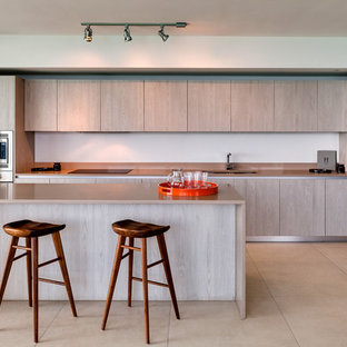 Large modern eat-in kitchen designs - Inspiration for a large modern single-wall beige floor eat-in kitchen remodel in Miami with an undermount sink, flat-panel cabinets, light wood cabinets, white backsplash, stainless steel appliances, an island and beige countertops