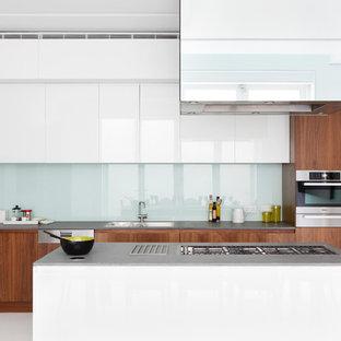 Esempio di una cucina parallela contemporanea con lavello da incasso, ante lisce, ante in legno scuro, paraspruzzi con lastra di vetro, isola, pavimento bianco e top grigio