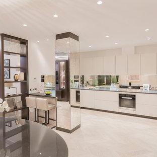 Inspiration for a contemporary open plan kitchen in London with flat-panel cabinets, white cabinets, metallic splashback, mirror splashback, stainless steel appliances, light hardwood flooring, a breakfast bar, beige floors and black worktops.