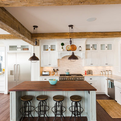 Example of a large farmhouse l-shaped dark wood floor and brown floor eat-in kitchen design in Cincinnati with white cabinets, white backsplash, stainless steel appliances, an island, a farmhouse sink, marble countertops, porcelain backsplash and shaker cabinets