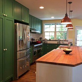 Large contemporary eat-in kitchen ideas - Inspiration for a large contemporary l-shaped medium tone wood floor and brown floor eat-in kitchen remodel in Austin with white backsplash, subway tile backsplash, stainless steel appliances, an island, a farmhouse sink, shaker cabinets, green cabinets and wood countertops