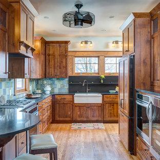 Foto di una cucina american style con ante con riquadro incassato, ante in legno scuro, paraspruzzi blu, elettrodomestici in acciaio inossidabile e pavimento in legno massello medio