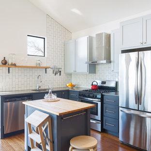 Klassisk inredning av ett litet l-kök, med en undermonterad diskho, bänkskiva i täljsten, vitt stänkskydd, stänkskydd i tunnelbanekakel, rostfria vitvaror, mellanmörkt trägolv, en köksö, skåp i shakerstil, blå skåp och orange golv