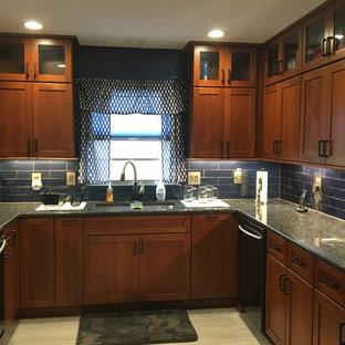 オーランドの中サイズのエクレクティックスタイルのおしゃれなコの字型キッチン (シングルシンク、シェーカースタイル扉のキャビネット、濃色木目調キャビネット、御影石カウンター、青いキッチンパネル、ガラスタイルのキッチンパネル、シルバーの調理設備の、セラミックタイルの床、アイランドなし、グレーの床、青いキッチンカウンター) の写真