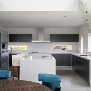 This is an example of a large contemporary u-shaped kitchen in Other with a submerged sink, flat-panel cabinets, grey cabinets, grey splashback, porcelain splashback, integrated appliances, porcelain flooring, an island, grey floors and grey worktops.